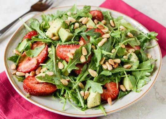 Салат из авокадо и клубники с поджаренными кедровыми орешками.
